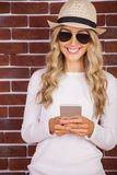 Gorgeous blonde hipster with sunglasses using smartphone Stock Photo