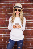 Gorgeous blonde hipster with sunglasses using smartphone Royalty Free Stock Photo