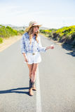 Gorgeous blonde hitchhiking on the road Royalty Free Stock Photos