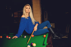 Gorgeous blonde lady plays billiard on the pool table Royalty Free Stock Images