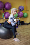 Gorgeous blonde lifting some weights and working on her arm muscles in a gym. Stock Photo