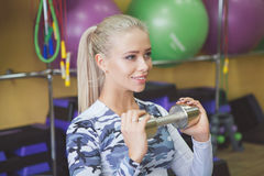 Gorgeous blonde lifting some weights and working on her arm muscles in a gym. Royalty Free Stock Photography