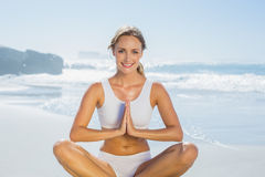 Gorgeous blonde in lotus pose by the sea Stock Images