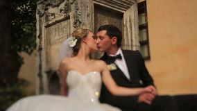 Gorgeous blonde newlywed bride and handsome groom kissing in front of old baroque building in Lviv. Sunny wedding day stock video