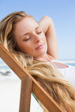 Gorgeous blonde sitting at the beach with eyes closed Royalty Free Stock Photo