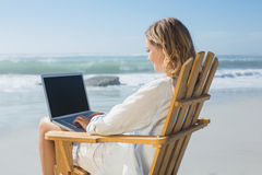 Gorgeous blonde sitting on deck chair using laptop on beach Stock Photography