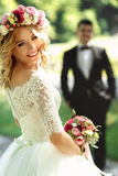 Gorgeous blonde smiling emotional bride in vintage white dress i Royalty Free Stock Image