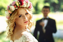 Gorgeous blonde smiling emotional bride in vintage white dress i Stock Images