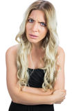 Gorgeous blonde wearing black dress frowning Royalty Free Stock Photography