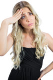 Gorgeous blonde wearing black dress suffering from headache Royalty Free Stock Images