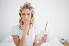 Gorgeous blonde wearing hair curlers covering her mouth Royalty Free Stock Image