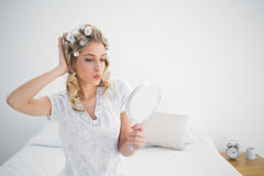 Gorgeous blonde wearing hair curlers kissing while looking at he Royalty Free Stock Image