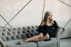 Gorgeous blonde woman in bright black dress on couch.