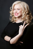 Gorgeous blonde woman emotionally toothy smiling and gesturing peace sign by fingers at camera. Female posing in studio. Girl with Stock Images
