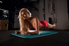 Beautiful blonde woman performing plank exercise. Gorgeous blonde woman with long hair, dressed in pink sports bra and shorts, performing plank with her forearms Royalty Free Stock Photography