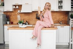 Gorgeous blonde woman in pink suit with loaf of bread on kitchen countrer.