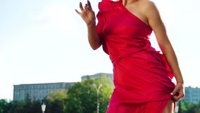 Gorgeous blonde woman in red dress dancing on street outside in slow motion. Professional dancer in urban environment. people, hobby and active lifestyle stock footage