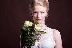 Gorgeous blonde woman in victorian dress with roses in hands Stock Photo
