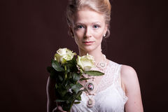 Gorgeous blonde woman in victorian dress with roses in hands Royalty Free Stock Photos