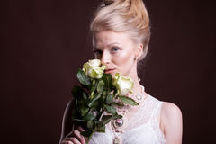 Gorgeous blonde woman in victorian dress with roses in hands Royalty Free Stock Images