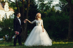 Gorgeous blonde young bride and charming groom holding hands at. Sunset in forest background Royalty Free Stock Photos
