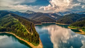 OUTSTANDING REFLECTION OF THE CLOUDY SKY OVER A MOUNTAIN LAKE royalty free stock image