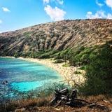 Blue Hawaiian water on beach with mountain Stock Image