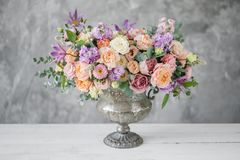 Gorgeous bouquet of different flowers. floral arrangement in vintage metal vase. table setting. lilac and peach color.  royalty free stock photos