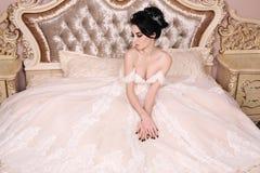 Gorgeous bride with dark hair in luxuious wedding dress. Fashion studio photo of gorgeous bride with dark hair in luxuious wedding dress stock images