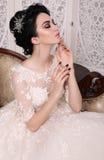 Gorgeous bride with dark hair in luxuious wedding dress. Fashion studio photo of gorgeous bride with dark hair in luxuious wedding dress royalty free stock photography