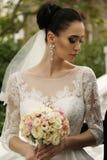 Gorgeous bride with dark hair wears elegant wedding dress. Fashion outdoor photo of gorgeous bride with dark hair wears elegant wedding dress, posing in park stock photos