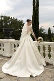 Gorgeous bride with dark hair wears elegant wedding dress Royalty Free Stock Photo