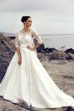 Gorgeous bride with dark hair wears elegant wedding dress Royalty Free Stock Images