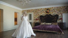 Gorgeous bride in dress walks in bedroom with smile at camera. 4K stock video