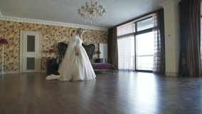 Gorgeous bride in dress walks in bedroom with smile. 4K stock video