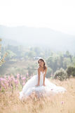 Gorgeous bride in elegant dress posing at sunny summer day on a background of mountains Stock Images