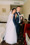 Gorgeous bride and elegant groom posing in hotel room after wedding ceremony. Portrait of newlyweds on honeymoon Stock Photography