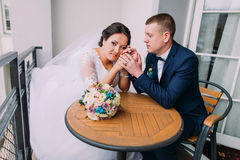 Gorgeous bride and elegant groom sit at the table on balcony having sweet moment. Newlyweds honeymoon concept Royalty Free Stock Image