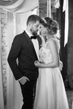 Gorgeous bride embraces groom while they are in the room. Couple standing against the light. Gorgeous bride embraces groom while they are standing in the room Stock Photo