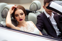 Gorgeous bride with fashion makeup and hairstyle in a luxury wedding dress with handsome groom near white cabriolet car Stock Images