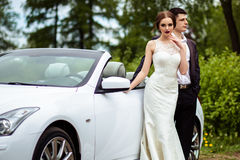 Gorgeous bride with fashion makeup and hairstyle in a luxury wedding dress with handsome groom near white cabriolet car Stock Photo