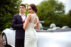 Gorgeous bride with fashion makeup and hairstyle in a luxury wedding dress with handsome groom near white cabriolet car Royalty Free Stock Images