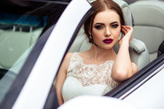 Gorgeous bride with fashion makeup and hairstyle near luxury wedding dress near white cabriolet car Royalty Free Stock Photography