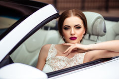 Gorgeous bride with fashion makeup and hairstyle near luxury wedding dress near white cabriolet car Stock Photo