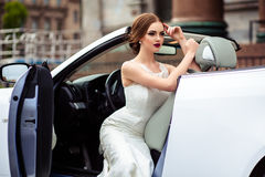 Gorgeous bride with fashion makeup and hairstyle near luxury wedding dress near white cabriolet car royalty free stock photos