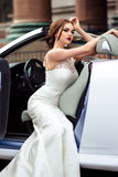 Gorgeous bride with fashion makeup and hairstyle near luxury wedding dress near white cabriolet car stock image