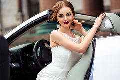 Gorgeous bride with fashion makeup and hairstyle near luxury wedding dress near white cabriolet car stock photography