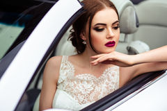 Gorgeous bride with fashion makeup and hairstyle near luxury wedding dress near white cabriolet car royalty free stock image