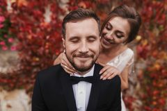 Gorgeous bride gently hugging stylish groom at old wall of autumn red leaves. Happy sensual wedding couple embracing. Romantic mo stock images
