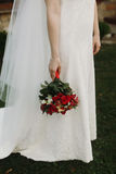 Gorgeous bride holding wedding bouquet of red roses orchids at g. Own dress. stylish wedding couple posing outdoors. tender sensual moment. floral arrangements Stock Photos